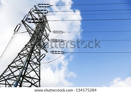 Low angle shot of a high-voltage electricity pylon and power lines, on the background of the blue & white cloudy sky. - stock photo
