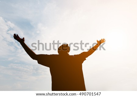 Low angle shot of a silhouetted man, with arms outstretched in joy, against the glaring light of the sun in a blue sky.