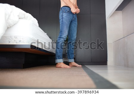 Low angle shot of a young man putting his jeans, he is standing by the bed in bedroom.