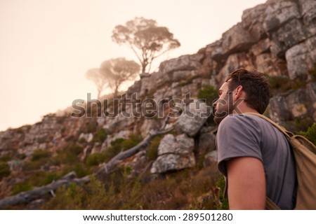 Low angle shot of a young man walking on a nature trail with a view of the misty mountain top beyond him - stock photo