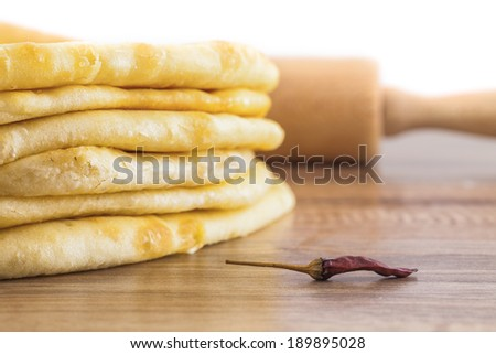 Low angle shot of baked pastry and a pepper with a rolling pin behind. - stock photo