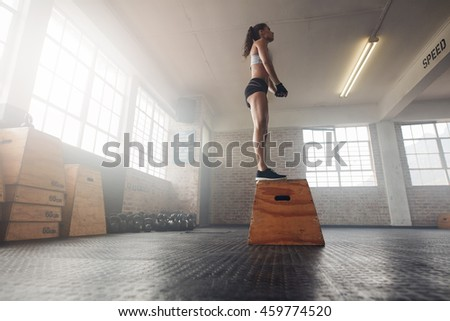 Low angle shot of fit young female model in sports wear standing on a box at gym. Muscular woman doing box jump exercise at gym. - stock photo