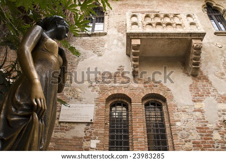 Low angle shot of statue of Juliet, with balcony in the background. - stock photo
