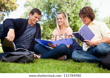 Low angle-shot of three students in a park studying - stock photo