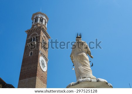 Low angle shot of Torre dei Lamberti in Piazza delle Erbe in Verona, with Marble statue in the foreground. - stock photo