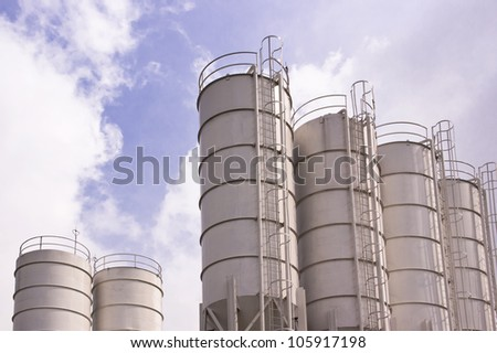Low angle shot of white industrial silos - stock photo