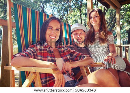 Low angle side shot of happy and positive company of people posing at the camera while sitting on comfortable summer beach chairs. Woman sitting on her man's knees