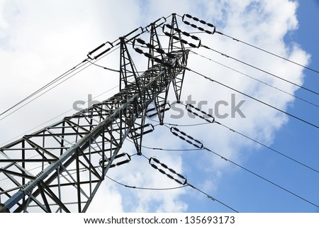 Low angle tilted shot of a high-voltage electricity pylon and power lines, on the background of the blue & white cloudy sky.