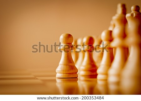 Low angle view across the surface of a chess board of a single wooden pawn in a chess game standing in front of the rest of the set in a game of skill, with copyspace - stock photo
