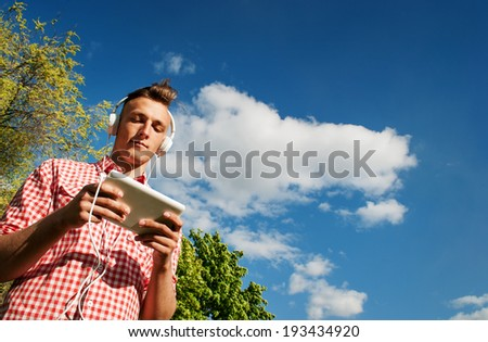 Low angle view against blue sky of a young man listening to music on his MP3 player standing searching through his library of tunes while listening on his headphones - stock photo
