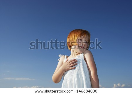 Low angle view delighted cute little girl with hand on chest looking away against blue sky