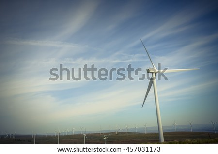 Low angle view group of wind turbines towers again cloud blue sky on a wind farm at Ellensburg, Washington, US. Clean, sustainable, renewable energy concept. Alternative energy source from wind power.