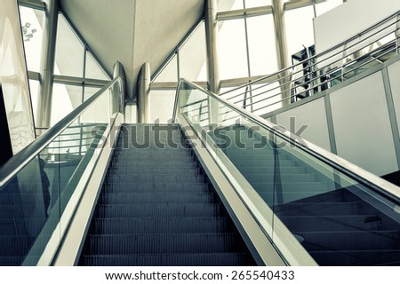 Low angle view looking to top of modern escalator with blue tone.