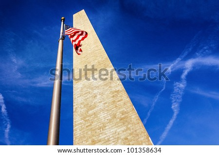 Low angle view looking to top of Washington monument with American flag, blue sky and cloudscape background. - stock photo