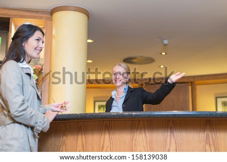 Low angle view of a beautiful friendly smiling receptionist behind the service desk in a hotel lobby helping an attractive female guest indicating with her hand the way to her accomodation - stock photo
