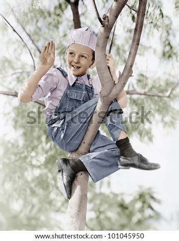 Low angle view of a boy sitting on a tree - stock photo