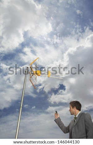 Low angle view of a businessman pointing cellphone at aerial against sky - stock photo