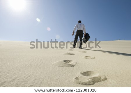 Low angle view of a businessman walking with briefcase in desert - stock photo