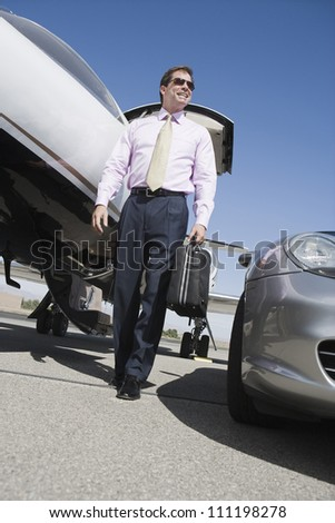 Low angle view of a businessman walking with briefcase on airfield - stock photo