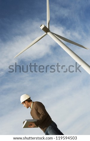 Low angle view of a Caucasian male engineer with clipboard against wind turbine and cloudy sky