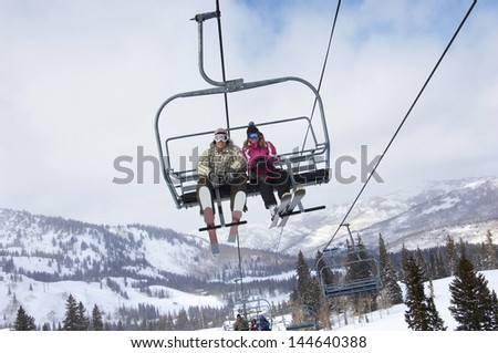 Low angle view of a couple in skies sitting on ski lift - stock photo