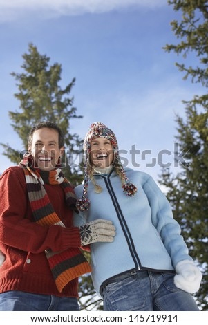 Low angle view of a couple in warm clothing laughing against the sky - stock photo