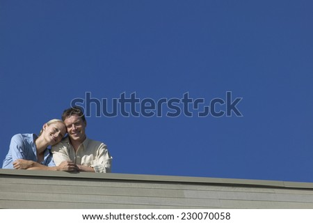 Low angle view of a couple looking out from the roof of their house - stock photo