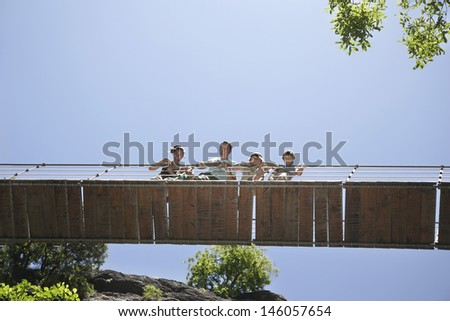 Low angle view of a couple with three children looking down from bridge against clear blue sky - stock photo