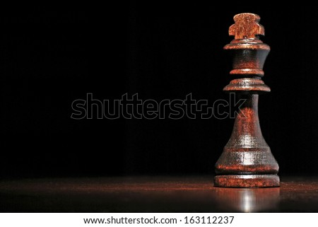 Low angle view of a dark wood king chess piece on a reflective wooden surface against a dark background with copyspace