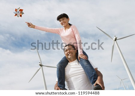 Low angle view of a father giving piggyback ride to daughter against windmill and cloudy sky - stock photo