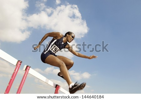Low angle view of a female athlete jumping hurdle - stock photo