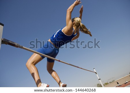 Low angle view of a female high jumper in midair over bar against blue sky - stock photo