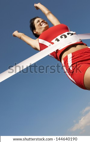 Low angle view of a female runner winning race against the blue sky - stock photo