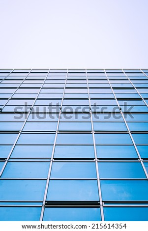 Low angle view of a glass and steel skyscraper giving the appearance of a futuristic landscape.