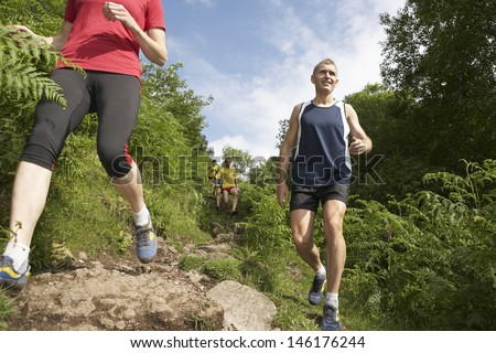 Low angle view of a group hiking down on trail - stock photo
