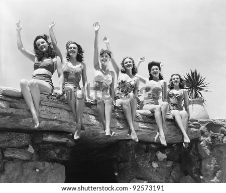 Low angle view of a group of women sitting on a stone structure and waving their hands - stock photo
