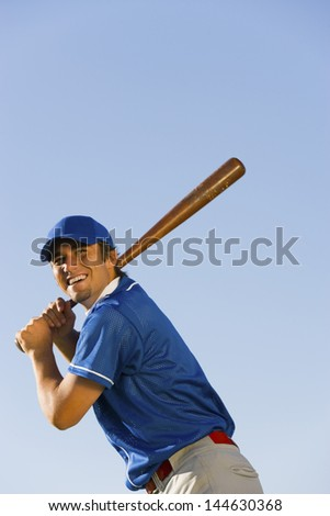 Low angle view of a happy baseball player swinging baseball bat against clear blue sky - stock photo