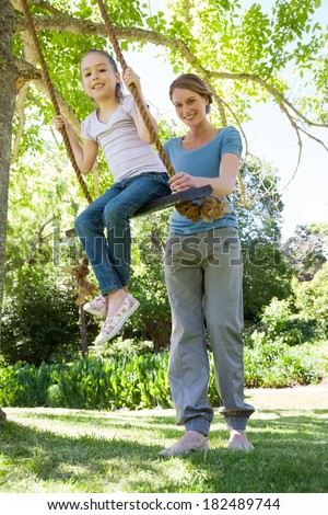 Low angle view of a happy mother swinging daughter at the park - stock photo