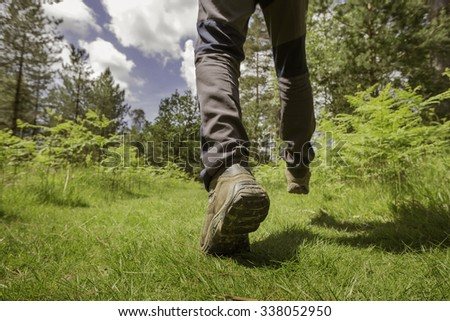 Low angle view of a hiker's legs and boots walking in a forest. - stock photo