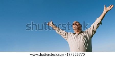 Low angle view of a joyful senior man rejoicing in the sunshine standing smiling happily with his arms outspread, horizontal banner format with copyspace