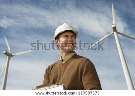 Low angle view of a male architect looking away against wind turbine and cloudy sky