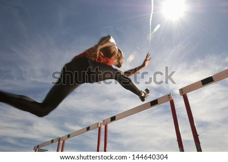 Low angle view of a male athlete jumping hurdle against the sky - stock photo
