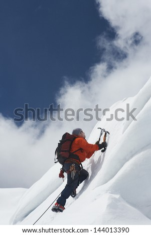 Low angle view of a male mountain climber going up snowy slope with axes against clouds - stock photo