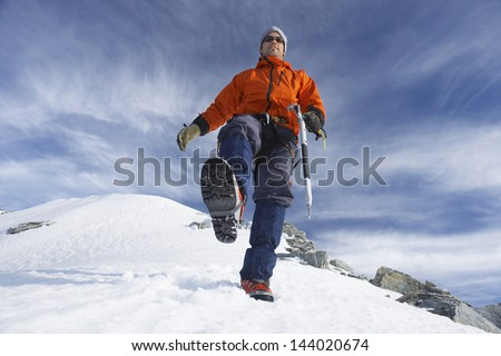 Low angle view of a male mountain climber hiking on snowy slope - stock photo