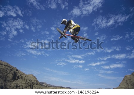Low angle view of a man on mountain bike jumping against blue sky - stock photo