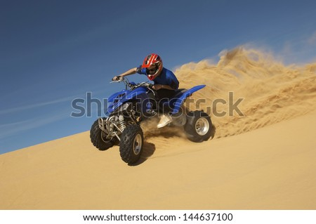 Low angle view of a man riding quad bike in desert against the blue sky - stock photo
