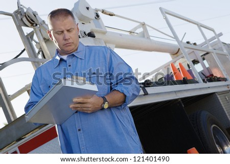 Low angle view of a mechanic writing notes on clipboard against a truck - stock photo