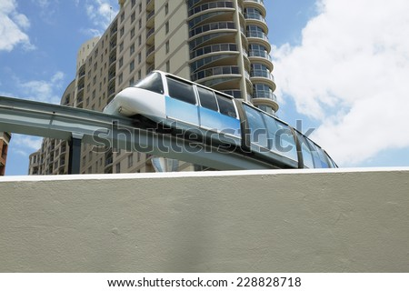 Low angle view of a monorail passing in front of an apartment building - stock photo
