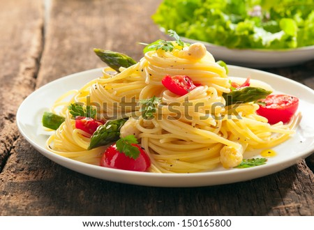Low angle view of a plate of Italian spaghetti with fresh green asparagus spears and tomato served with a leafy green salad - stock photo