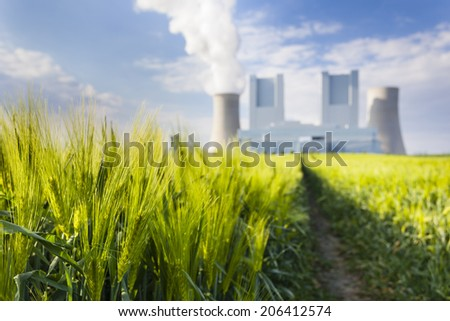 Low angle view of a shiny new lignite power station behind a rye field with wheel tracks leading to it. Focus on the rye.